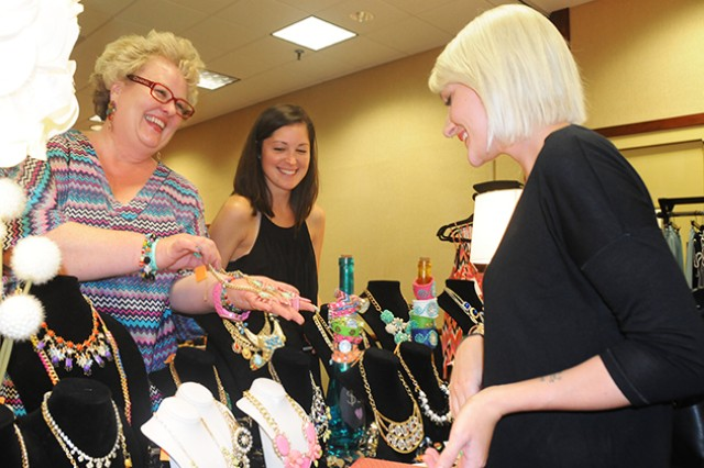 Kim Kozel, Dandy Lion Boutique employee, presents a necklace to Brittany Ernst, Army spouse, at the sixth biannual Fort Rucker Girls Night Out Sept. 6.