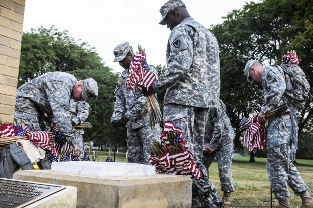 """Soldiers of Rock Island Arsenal, Ill., place flags in the ground following an early-morning 3.25-mile walk in a """"field of honor"""" across the street from RIA's Memorial Field off Rodman Avenue. The field of honor will remain until after reveille, Sept. 13."""