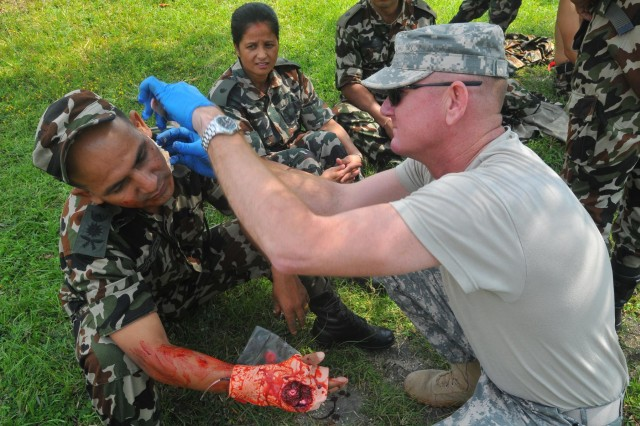 Participants in the Nepal Pacific Resilience Disaster Response Exercise & Exchange, or DREE, moulage role-players in preparation for the search and rescue operations during the second day of the exercise, Sept. 10, 2013, in Kathmandu, Nepal. The DREE, co-hosted by the Nepalese army and U.S. Army Pacific, runs Sept. 9-12, and it is the first in Nepal to include a field training exercise designed to practically apply civil-military disaster preparedness and response initiatives when faced with a massive earthquake scenario.