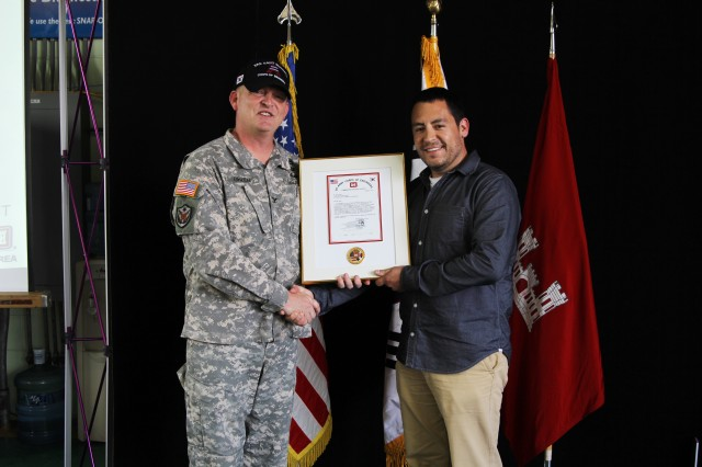 Civil Engineer Jacob West receives the Chief of Engineers 2011 Military Contingency Responder of the Year award from Col. Bryan S. Green, U.S. Army Corps of Engineers Far East District commander, on behalf of Chief of Engineers Lt. Gen. Thomas P. Bostick, Aug. 30. West received the award for his service in Afghanistan between late 2010 and 2012.