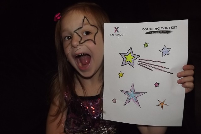 This photograph won first prize in the age 5 to 8 category of the Army and Air Force Exchange Service Cutest Kiddo (Coloring) Contest. The photograph features USAG Bamberg kindergartener Paris Stupar holding up her coloring contest sheet.