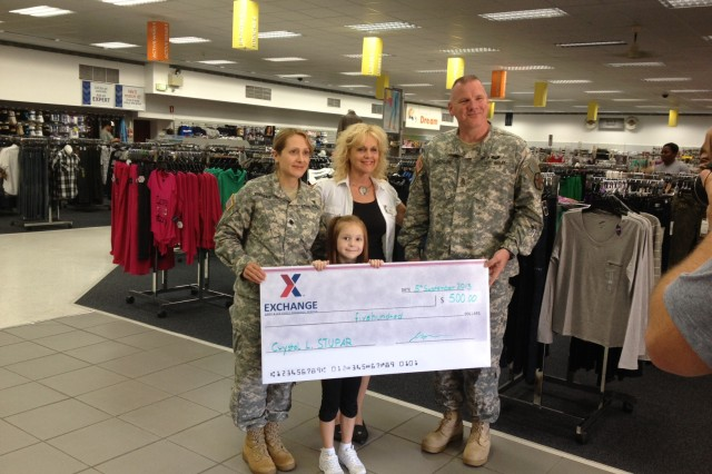 """Paris Stupar, front center, won first place in her age division in the Army & Air Force Exchange Service's """"Cutest Kiddo"""" contest. She was presented with a $500 Exchange gift card by Lt. Col. Michelle Bienias, garrison commander, Command Sgt. Maj. William Funcheon, garrison command sergeant major, and Bamberg Exchange manager Eileen Al-Sayed."""