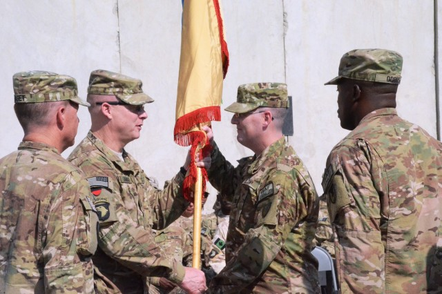 Brig. Gen. Duane Gamble, deputy commanding general of 1st Theater Support Command (Forward), passes the colors to Col. Edward Burke, 401st Army Field Support Brigade's incoming commander, during a change of command ceremony, Sept. 9, at Bagram Airfield, Afghanistan. (Photo by Sharonda Pearson, 401st AFSB Public Affairs)