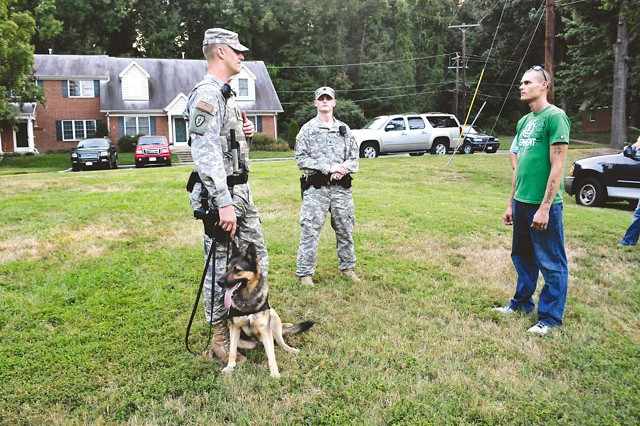 Staff Sgt. Kyle Fenstermacher (left), 947th Military Police Detachment, 289th MP Battalion; pauses with Riko, a military working dog, and Sgt. Nicholas Snook (center), 212th Military Police Detachment, to speak with Fort Belvoir resident Spc. Ryan Crittenden (right), 529th Regimental Support Company, 4th Battalion, 3rd U.S. Infantry Regiment, during a walking patrol of Dogue Creek Village Aug. 30.
