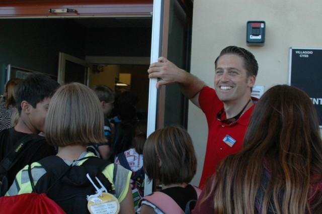John-Luca Harbeson, Youth Center director, holds open the door to the new facility following a  ribbon-cutting ceremony for the new Youth Center on Villaggio Sept. 9. The center cost nearly $5 million to build and can accommodate 150 teens from sixth-twelfth grade.