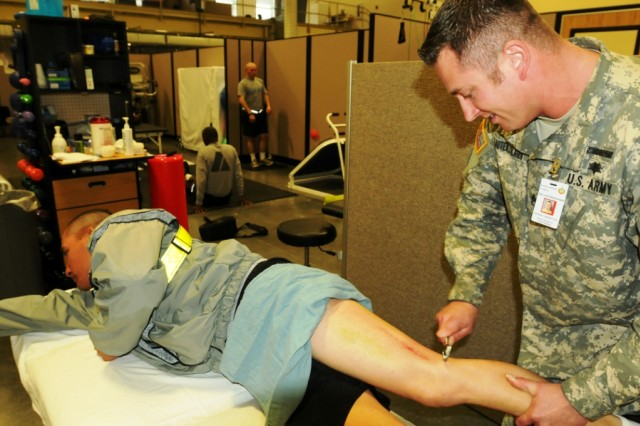 Staff Sgt. Adam Lautenschlager works on a physical therapy regimen with Spc. Enrique Rivera at the Army's first Soldier Centered Medical Home, on Joint Base Lewis-McChord North, Wash. The concept of the Soldier Centered Medical Home is to address medical readiness issues for brigades by consolidating battalion aid station resources with some clinic capabilities.