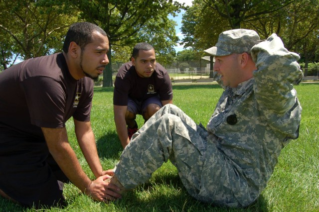 Listening to instructions, fraternal twin brothers Edward (left) and Jacob (center mass) Maldonado listen very carefully to their physical fitness instructor, Staff Sgt. Matthew Johnson, as he leads them through a demonstration of how to perform properly the situp portion of the Army Physical Fitness Test.