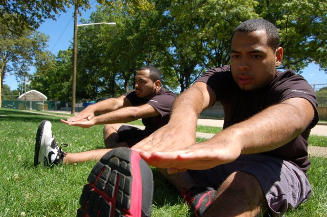 Performing the hamstring strech seated, Jacob Maldonado (right), and his twin brother, Edward (left), who hail from Long Island City, Queens, N.Y., attempt to elongate their muscles in preparation for physical training.