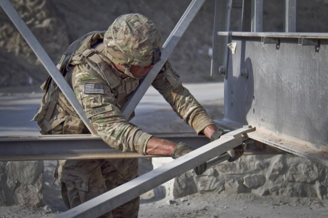 A U.S. Army soldier with the 1438th Engineer Multi-Role Bridge Company, from the Missouri National Guard, uses a wrench to loosen the bolt of a transom while constructing a Mabey-Johnson bridge in the village of Laka Tiza, Afghanistan, Sept. 2, 2013. (U.S. Army photo by Sgt. Justin A. Moeller, 4th Brigade Combat Team Public Affairs)