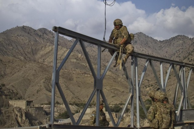 A U.S. Army soldier with the 1438th Engineer Multi-Role Bridge Company, from the Missouri National Guard, prepares to hook up a section of bridge to an excavator to assist in the construction, in the village of Laka Tiza, Afghanistan, Sept. 2, 2013. (U.S. Army photo by Sgt. Justin A. Moeller, 4th Brigade Combat Team Public Affairs)