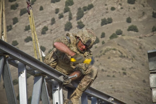 A U.S. Army soldier with the 1438th Engineer Multi-Role Bridge Company, from the Missouri National Guard, uses a mallet and bolt to knock a pin loose during the construction of a Mabey-Johnson bridge, in the village of Laka Tiza, Afghanistan, Sept. 2, 2013. (U.S. Army photo by Sgt. Justin A. Moeller, 4th Brigade Combat Team Public Affairs)