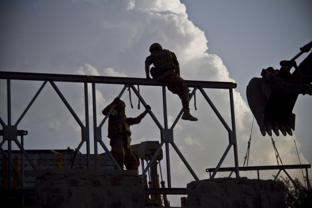 U.S. Army soldiers with the 1438th Engineer Multi-Role Bridge Company, from the Missouri National Guard, prepare to hook up a section of bridge to an excavator to assist in the construction, in the village of Laka Tiza, Afghanistan, Sept. 2, 2013. (U.S. Army photo by Sgt. Justin A. Moeller, 4th Brigade Combat Team Public Affairs)