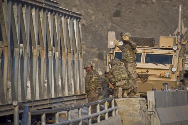 An U.S. Army soldier with the 1438th Engineer Multi-Role Bridge Company, from the Missouri National Guard, monitors the progress of a Mabey-Johnson bridge using hand signals, as it rolls across the span it is intended to cover, near the village of Laka Tiza, Afghanistan, Sept. 2, 2013. (U.S. Army photo by Sgt. Justin A. Moeller, 4th Brigade Combat Team Public Affairs)