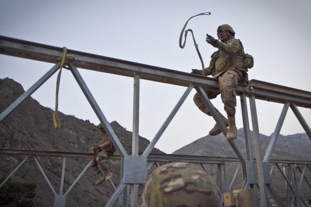 U.S. Army soldiers with the 1438th Engineer Multi-Role Bridge Company, from the Missouri National Guard, prepare to hook up a section of bridge to an excavator to assist in the construction in the village of Laka Tiza, Afghanistan, Sept. 2, 2013. (U.S. Army photo by Sgt. Justin A. Moeller, 4th Brigade Combat Team Public Affairs)
