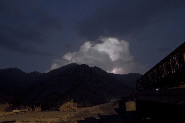With a lightning storm approaching, U.S. Army soldiers from Gunfighter Company, 1st Battalion, 506th Infantry Regiment, 4th Brigade Combat Team, provide security for the 1438th Engineer Company, Multi-Role Bridge, Missouri National Guard, as they construct a Mabey-Johnson bridge in the Khowst - Gardez Pass, Paktya province, Afghanistan, Sept. 2, 2013. (U.S. Army photo by Sgt. Justin A. Moeller, 4th Brigade Combat Team Public Affairs)