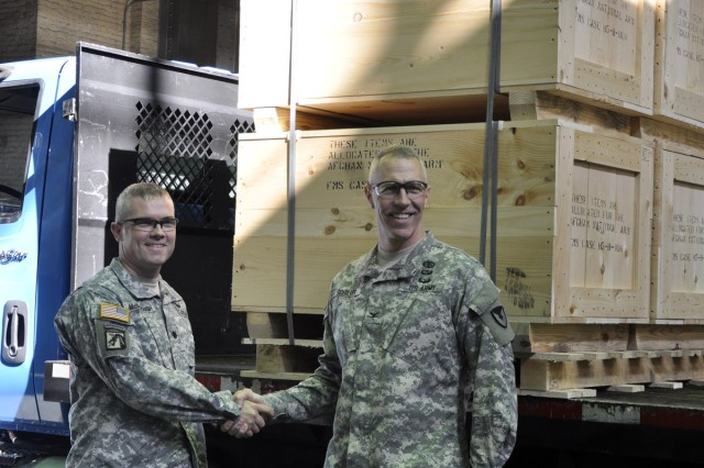 Final crates loaded on a truck signify great success to Army Program Manager Lt. Col. William McDonough, left, and Arsenal Commander Col. Lee H. Schiller Jr.