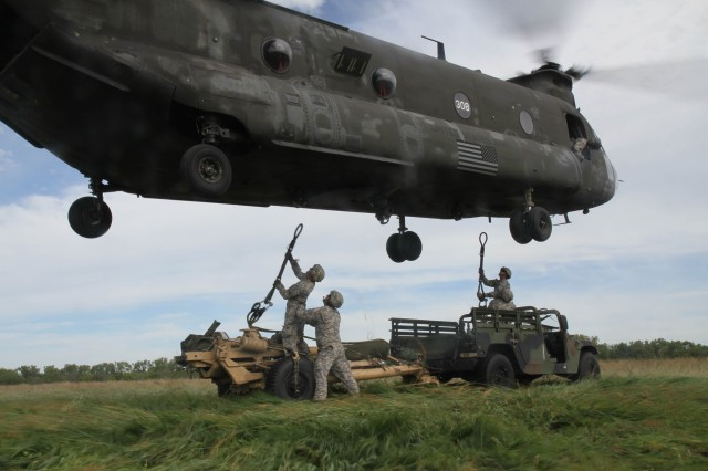 Staff Sgt. David De La O, 1st Sgt Scott Benge, Staff Sgt. Joshua Smith and Staff Sgt. Adam Hartle, all assigned to Battery B, 2 Bn., 32nd FA Reg., team up and brace each other from the high winds of the CH-47 Chinook propellers while successfully hooking up their M119A lightweight howitzer and its high mobility multipurpose wheeled vehicle and transporting them to an alternate location on Fort Riley from Marshall Airfield Sept. 13. This air assault sling load training exercise reaffirms that the teams can effectively move multiple pieces of equipment without loss or destruction of government property.