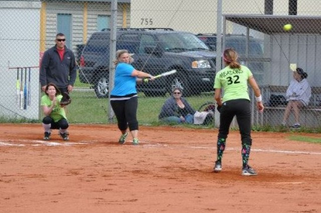 Jessica Meadows pitches one to batter Teresa Powell, with Jackie Moses as catcher and Brett Meadows acting as umpire during one of the games of the Hohenfels Community Softball League.