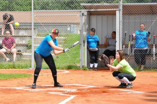 Gabi Pierce takes a swing while catcher Jackie Moses sets up behind her during one of the games of the Hohenfels Community Softball League.