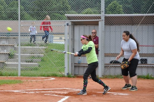 Jessica Meadows blasts the ball while catcher Angie Ueligitone watches during one of the games of the Hohenfels Community Softball League.