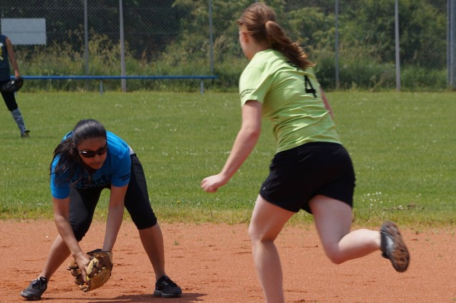 Angelica Avila catches the grounder while high-schooler Bianca Hascin runs for the base during one of the games of the Hohenfels Community Softball League.
