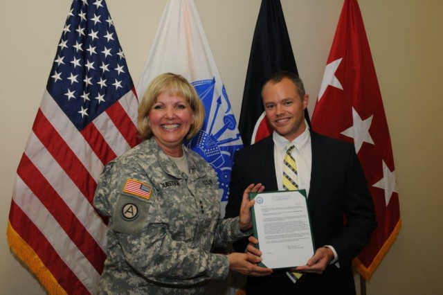 Lt. Gen. Patricia McQuistion, deputy commanding general of AMC, presents Michael James Pauly, Army Materiel Command employee, with his certification making him the 92nd Army professional to receive the Lean Six Sigma Master Black Belt Certification. U.S. Army Photo by: Doug Brewster.