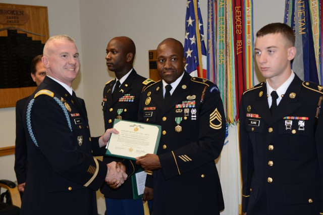 Sgt. 1st Class Daryl B. Williams Jr. receives the Army Commendation Medal from Col. James C. Markert, 3rd Infantry Regiment (The Old Guard), regimental commander, for his actions as a first responder during a traffic accident in Washington. The Soldier is from the 289th Military Police Company, 3rd U.S. Infantry Regiment (The Old Guard). The ceremony was held at the Old Guard Headquarters building, Joint Base Myer-Henderson Hall, Va., Sept. 13, 2013.