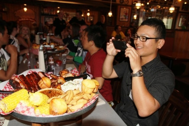 Japan Ground Self Defense Force Sgt. Junya Takahara takes a picture of the food served at a barbecue restaurant Sept. 15, 2013, near Joint Base Lewis-McChord, Wash.  (U.S. Army Staff Sgt. Mark Miranda/Released)