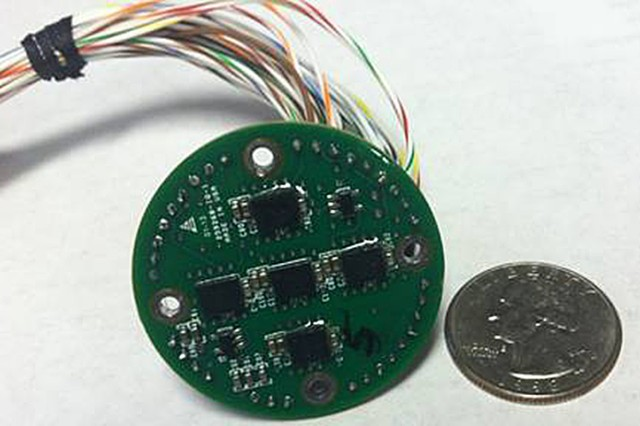 A sensor array next to a quarter to reflect relative size.