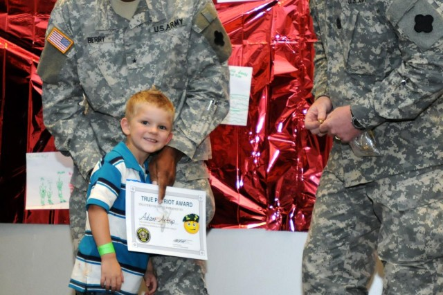 """Army Reserve child Adam Artrip receives a """"True Patriot Certificate"""" from Brig. Gen. Alton G. Berry, deputy commanding general of the 88th Regional Support Command, and Command Sgt. Maj. David Unseld, command sergeant major of the 88th RSC, during an award ceremony held at a Yellow Ribbon Event in Rosemont, Ill., Sept. 14. """"The children have a purpose [at Yellow Ribbon Events]. They do get their fun time, but they also get training and are recognized for their actions,"""" said Berry. """"This lets the parents know the kids have done what was asked of them, plus any time you can recognize a kid - it has value."""" The 88th Regional Support Command hosted more than 400 deploying and recently re-deployed Army Reserve soldiers and their family members at the Yellow Ribbon Event which provides soldiers and their families with information, services, referrals, and outreach opportunities throughout the entire deployment cycle. (Photo by Sgt. 1st Class C.L. Beal, 88th RSC Public Affairs chief)"""