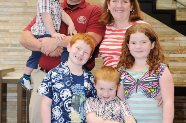 "First Lt. Brice Bennett, who recently returned from deployment to Afghanistan as chaplain of the 384th Military Police Battalion, stands with his wife Melissa and three children during a Yellow Ribbon Event in Rosemont, Ill., Sept. 14. ""Yellow Ribbon is absolutely integral to Army Reserve families,"" said Melissa. ""Otherwise the families are left out of almost everything and we don't have any way to connect and know what's going on."" The 88th Regional Support Command hosted more than 400 deploying and recently re-deployed Army Reserve soldiers and their family members at the Yellow Ribbon Event which provides soldiers and their families with information, services, referrals, and outreach opportunities throughout the entire deployment cycle. (Photo by Sgt. 1st Class C.L. Beal, 88th RSC Public Affairs chief)"