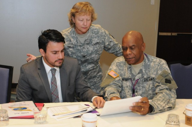 """Outreach coordinator for Illinois Congresswoman Tammy Duckworth, Omar Aquino, receive a brief on the Army Reserve by Brig. Gen. Alton G. Berry, deputy commanding general of the 88th Regional Support Command, and Col. Rhonda Smillie, legislative liaison of the 88th RSC, while visiting a Yellow Ribbon Event in Rosemont, Ill., Sept. 14. """"It sends a powerful message to our soldiers and their families when our elected officials and their representatives take the time to attend events such as Yellow Ribbon,"""" said Smillie. """"It also provides an opportunity for our leaders to discuss our strategic goals and way-ahead for the Army Reserve."""" The 88th Regional Support Command hosted more than 400 deploying and recently re-deployed Army Reserve soldiers and their family members at the Yellow Ribbon Event which provides soldiers and their families with information, services, referrals, and outreach opportunities throughout the entire deployment cycle. (Photo by Sgt. 1st Class C.L. Beal, 88th RSC Public Affairs chief)"""