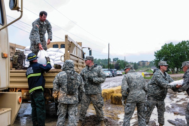 Soldiers and Airmen from the Colorado National Guard, along with members of civilian emergency response agencies, distribute sandbags to overly saturated areas of Jefferson County, Colo., Sunday.