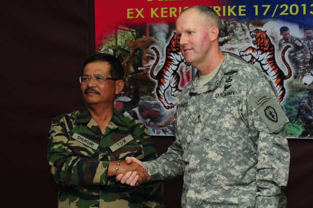 Brig. Gen. Pete Johnson, Deputy Commanding General-Operations of the 25th Infantry Division, shakes hands with Maj. Gen. Dato Mohd Shukuri bin Ahmad, the General Officer Commanding of the Malaysian Army 2nd Infantry Division, after the Keris Strike 13 Opening Ceremony press conference at Lapangan Terbang Camp, Sungai Petani, Kedah, Malaysia Sept. 17. Keris Strike is a U.S. Army Pacific-sponsored Theater Security Cooperation Program exercise conducted annually with the Malaysian Armed Forces designed to strengthen the military ties between the two countries. (U.S. Army photo by Staff Sgt. Sean Everette)