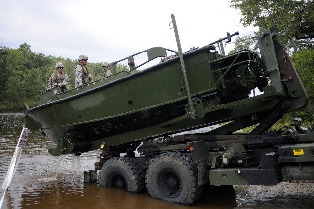 Staff Sgt. Seth Herriman (center left) and Staff Sgt. Paul Pipic wait for their bridge erection boat to lower onto the common bridge transporter. The Soldiers tested the new tactical boat launch at White's Lake, Fort A.P. Hill, Va.