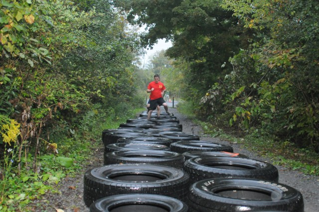 Members of 7th Engineer Battalion hop through tires during the first obstacle of the Mountain Mudder.