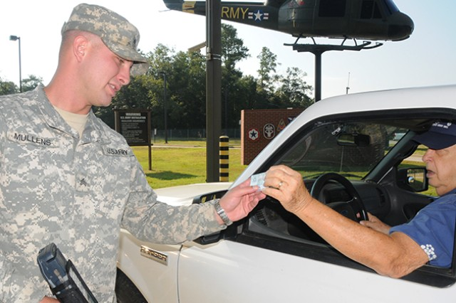 Sgt. Spencer Mullen, 1-58th Airfield Operations Battalion, checks the identification cards of people seeking access to Fort Rucker at the Enterprise gate Sept. 17.