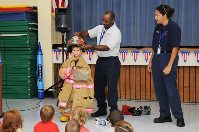 Children look on as Anthony Hayes, captain of the Fort Rucker Fire Department, puts a firefighter's helmet on Harry Sessoms, FRPS kindergarten student, during an event to teach students about the importance of first responders Sept. 11.