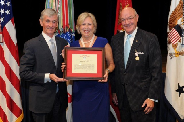 Secretary of the Army John McHugh presents Bridget Lamont, the wife of Thomas R. Lamont, the retiring assistant secretary of the Army for Manpower and Reserve Affairs, with the Secretary of the Army Public Service Award, the Pentagon, Sept. 19, 2013.