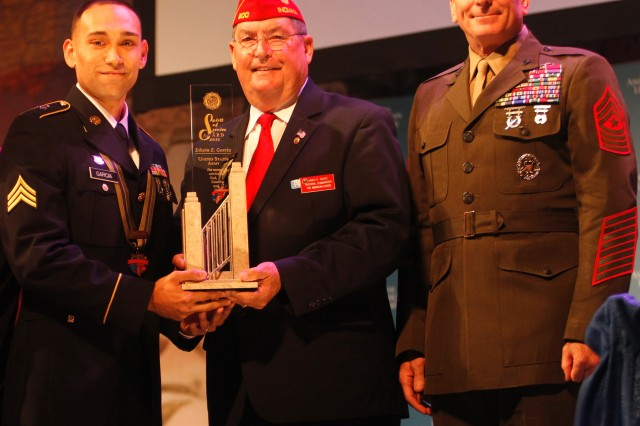 American Legion National Commander James E. Koutz and Sgt. Maj. Bryan B. Battaglia, U.S. Marine Corps Senior Enlisted Advisor to the Chairman of the Joint Chiefs of Staff, present the American Legion's Spirit of Service award to Sgt. Edwin Garcia, a veterinary food inspector at the USAPHC. The award was presented to Garcia in August for his extensive volunteer efforts