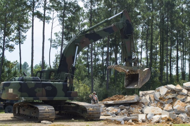 Mississippi Army National Guard Soldiers of the 838th Engineer Company complete a cumulative training exercise designed by First Army, planned and executed by 177th Armored Brigade trainer/mentors, in preparation for an October deployment to Afghanistan.  Mississippi and Alabama will attach to the Maine National Guard 133rd Engineer Battalion for the upcoming retrograde mission providing construction support. Soldiers clear large rubble and debris with a heavy equipment excavator. (U.S. Army photo by Spc. Karen Sampson, 177th Armored Brigade Public Affairs)