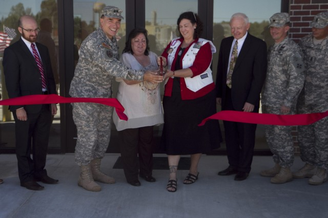 Assisted by Maj. Gen. Gill Beck Sr, commander of the 81st Regional Support Command, Mrs. Kay Jackson, left and Mrs. Amy Frost cut the ribbon during the memorialization and ribbon-cutting ceremony for the Spc. Christopher Fox Tactical Equipment Maintenance Facility on September 14 in Millington, Tenn. Mrs. Jackson is Fox's aunt and Mrs. Frost is his foster mother.