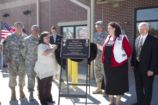 Mrs. Kay Jackson, left and Mrs. Amy Frost unveil the plaque during the memorialization and ribbon-cutting ceremony for the Spc. Christopher T. Fox Tactical Equipment Maintenance Facility on September 14 in Millington, Tenn. Mrs. Jackson is Fox's aunt and Mrs. Frost is his foster mother.
