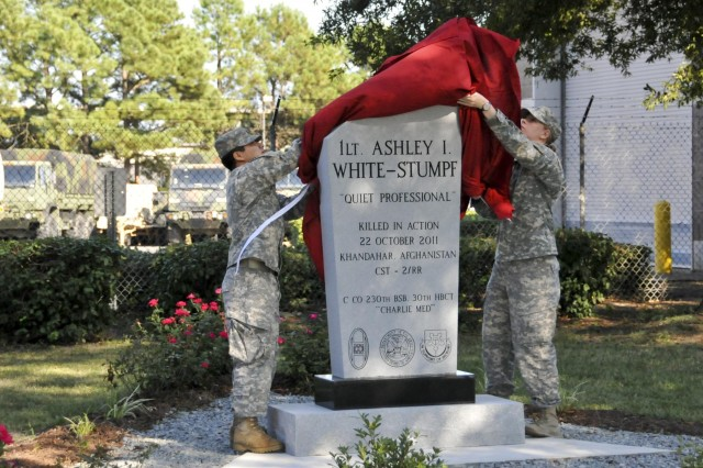 Soldiers with the 230th Brigade Support Battalion, 30th Armored Brigade Combat Team, North Carolina National Guard, unveil a monument in memory of 1st Lt. Ashley White-Stumpf at the Goldsboro National Guard Armory, N.C., Sept. 15, 2013. Red roses, said to have been White-Stumpf's favorite color and flower, surround the structure.  White-Stumpf was killed when the cultural support team she was serving with encountered an improvised explosive device in Afghanistan, October 22, 2011. (U.S. Army National Guard photo by Staff Sgt. Kelly S. LeCompte, 30th Armored Brigade Combat Team, NCNG/Released)