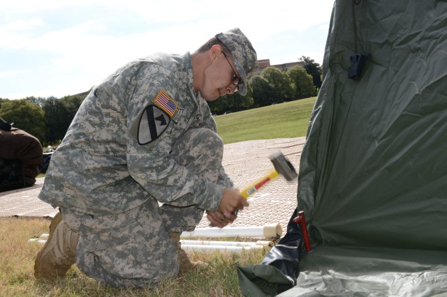 Spc. Brandon C. Scott, U.S. Army Military District of Washington G3 tasking specialist, hammers a stake into the ground to secure to the Deployable Rapid Assembly Shelter (DRASH), at Fort Lesley J. McNair, Washington DC, Sept. 17.