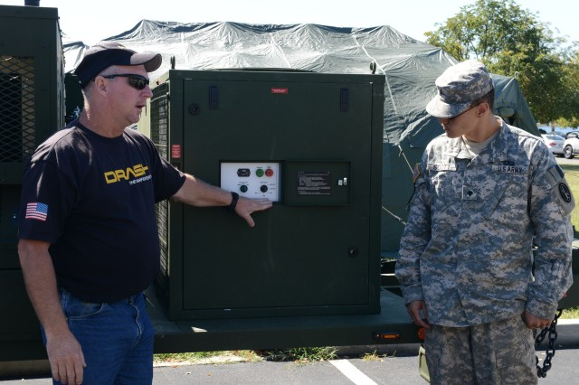 DRASH representative Willie Craig instructs Spc. Brandon C. Scott, U.S. Army Military District of Washington G3 tasking specialist, how to operate the Deployable Rapid Assembly Shelter (DRASH) generator, at Fort Lesley J. McNair, Washington DC, Sept. 17.