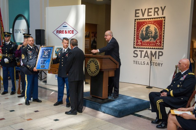 The command team from the 1st Battalion, 8th Infantry Regiment, 4th Infantry Division presents a plaque to Allen Kane, director of the National Postal Museum, during 1st Sgt. David McNerney Medal of Honor Enshrinement Ceremony at the Smithsonian National Postal Museum in Washington, D.C. Sept. 22, 2013. (U.S. Army photo by Staff Sgt. Teddy Wade/ Released)