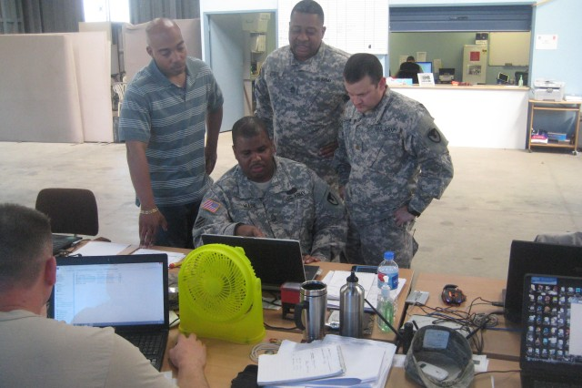 Sgt. 1st Class Daniel Dash, 411th Contracting Support Brigade, Master Sgt. Jerry Dysick, 411th CSB, and Maj. Charles Allen, 413th CSB, look on as Sgt. 1st Class Derrick Wade, 413th CSB, shows the group the status of existing contracts.
