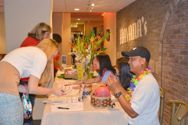 Guests check in and spouses of deployed Service members are given raffle tickets during the Deployed Spouse Luau at Havana's on Torii Station on Sept. 21, 2013.