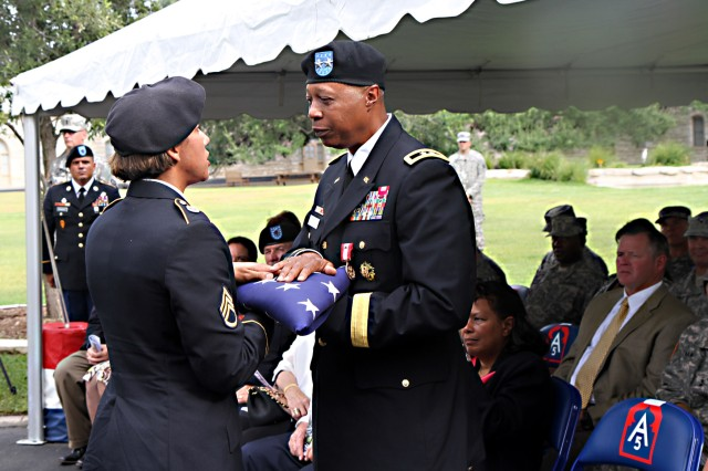 FORT SAM HOUSTON, Texas - Maj. Gen. Adolph McQueen Jr., deputy commanding general for support, U.S. Army North (Fifth Army), is presented an American flag from Staff Sgt. Erica McMillan, Headquarters Support Company, Headquarters and Headquarters Support Battalion, Army North, during McQueen's retirement ceremony Sept. 17 at the historic Quadrangle. The flag, which was flown over the Quadrangle, was given to McQueen as a final gesture of thanks for his service to the nation. McQueen retired from the Army after 41 years of service.
